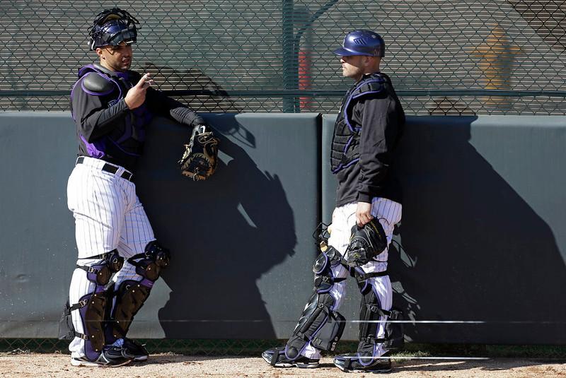. Colorado Rockies\' Gustavo Molina talks Ramon Hernandez, right, during a break in a spring training baseball workout Tuesday, Feb. 12, 2013, in Scottsdale, Ariz. (AP Photo/Darron Cummings)