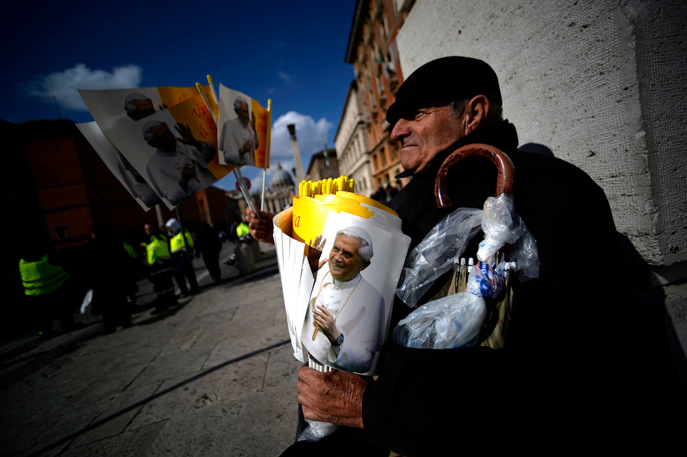 Description of . A man sells flags bearing a picture of Pope Benedict XVI's ahead of the Pope's last Angelus prayers before stepping down on February 24, 2013 at St Peter's Square in Vatican city. FILIPPO MONTEFORTE/AFP/Getty Images