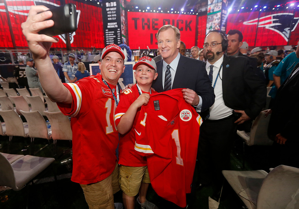 . Kansas City Chiefs fans Chris Miller and his son Zane, 12, of Platte City, Mo., pose for a photo with Commissioner Roger Goodell during the first round of the NFL football draft, Thursday, April 26, 2018, in Arlington, Texas. (AP Photo/Michael Ainsworth)