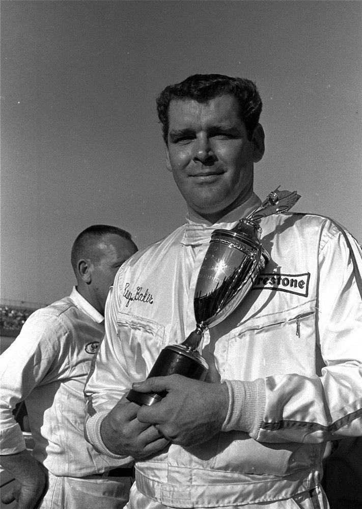 Description of . Buddy Baker, of Charlotte, NC, holds a trophy presented to him after he won the pole position on Februrary 9, 1969, for the Daytona 500 Grand National stock car race with a one lap speed of 188.901 miles per hour in his 1969 Dodge Charger. (AP Photo)