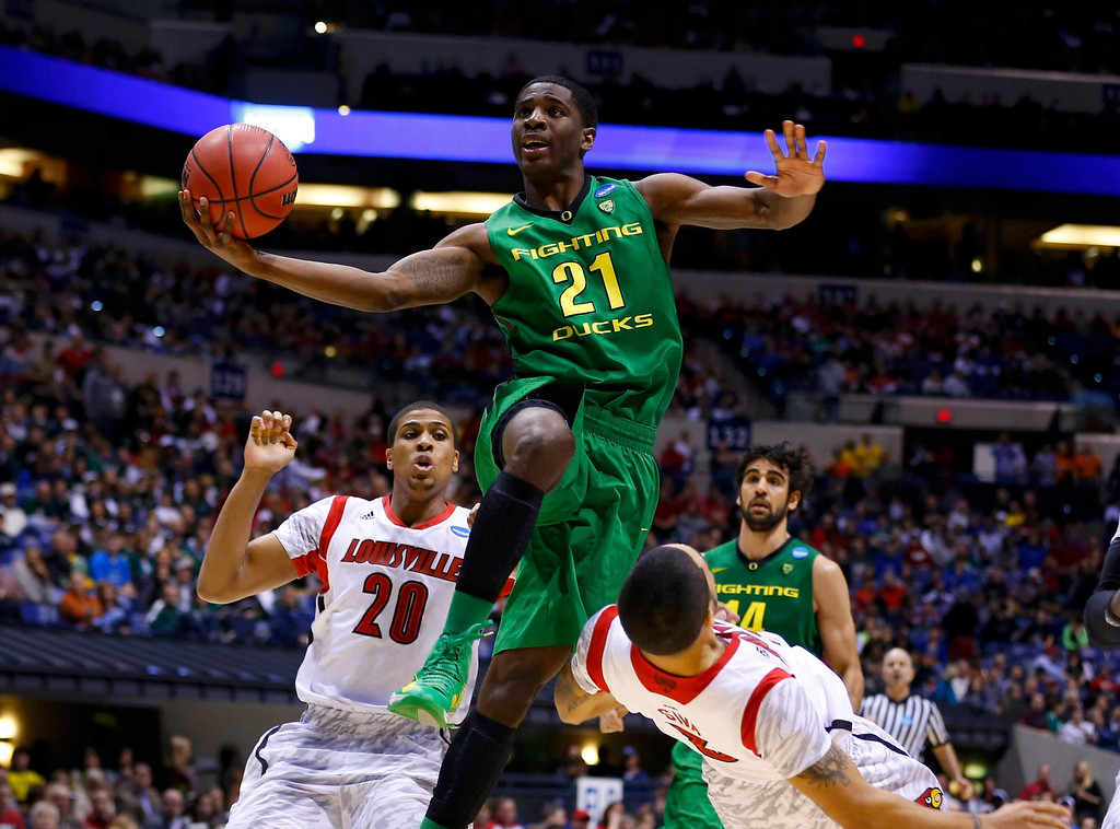 . Oregon Ducks guard Damyean Dotson (21) is called for the charge on Louisville Cardinals guard Russ Smith (2) as he goes to the basket in the second half during their Midwest Regional NCAA men\'s basketball game in Indianapolis, Indiana, March 29, 2013. REUTERS/Jeff Haynes