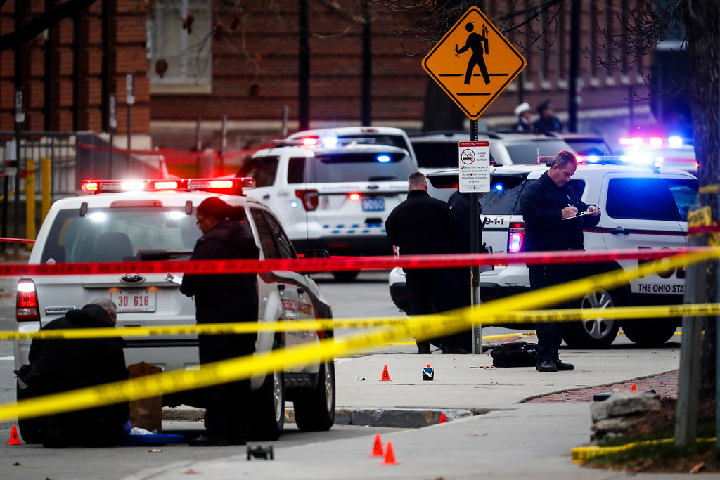 . Crime scene investigators collect evidence from the pavement as police respond to an attack on campus at Ohio State University, Monday, Nov. 28, 2016, in Columbus, Ohio. (AP Photo/John Minchillo)