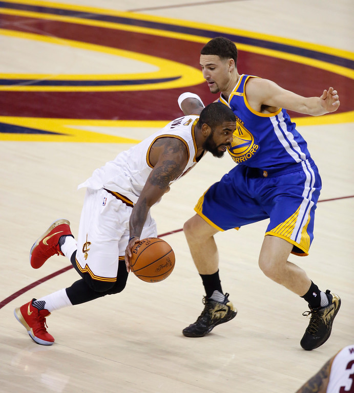 . Cleveland Cavaliers guard Kyrie Irving (2) drives on Golden State Warriors guard Klay Thompson (11) during the first half of Game 4 of basketball\'s NBA Finals in Cleveland, Friday, June 9, 2017. (AP Photo/Ron Schwane)