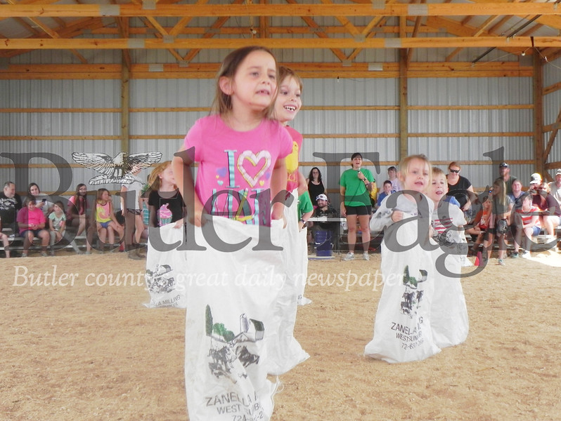 Evans City Elementary School second-grader Adelyn Clukey, 7, jumps as far as she can during the sack race in the Barnyard Olympics on Tuesday at the Butler Farm Show. Photo by Gabriella Canales.