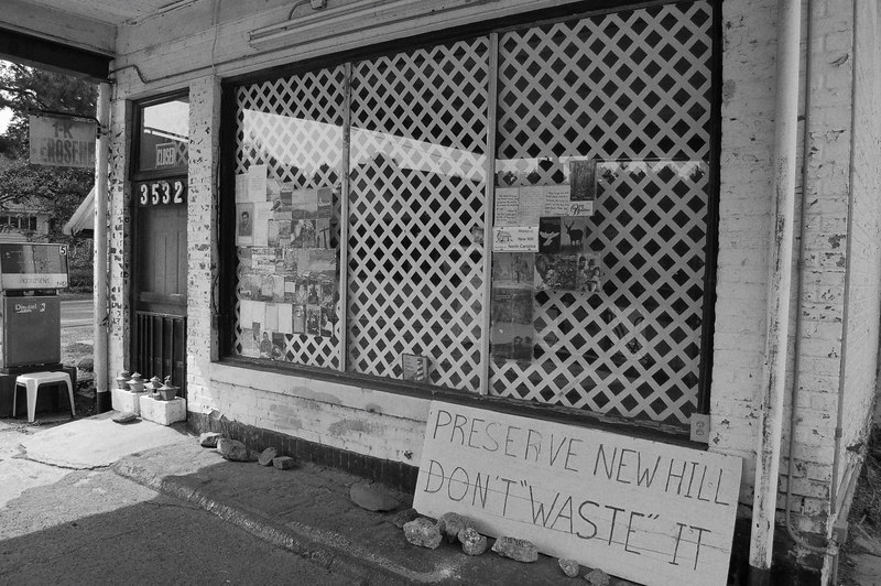 What used to be the storefront of this gas station now contains advertisements for the local church as well as a clear message to would-be vandals.
