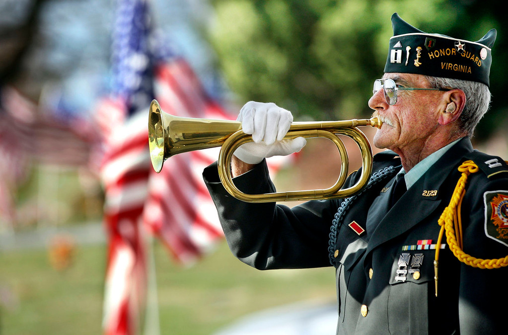 . Veterans of Foreign Wars Post 2123 Honor Guard member Ed Ellis plays taps Monday, Nov.11, 2013, during a Veterans Day Memorial Service held at Omps Funeral Home South Chapel in Shenandoah Memorial Park near Winchester, Va.(AP Photo/The Winchester Star, Scott Mason)