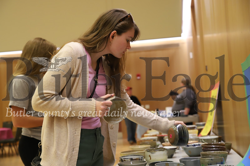 Slippery Rock junior Gabriella McAdams, 21, selectively picks her bowl at Friday's Empty Bowls event. The soup dinner promotes awareness for food insecurity issues on college campuses.