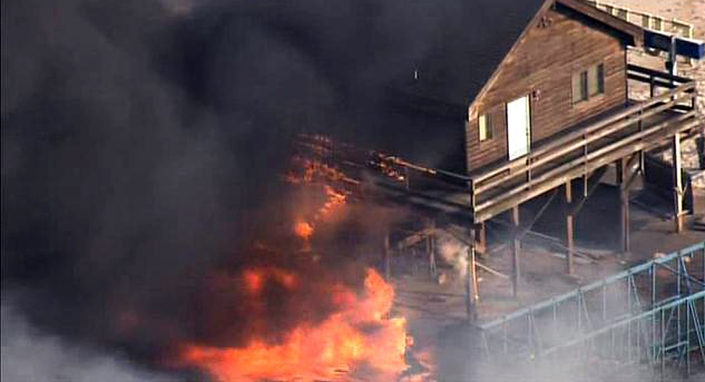 Description of . Flames engulf a building on the boardwalk in the resort community of Seaside Park, N.J., Thursday, Sept. 12, 2013. The massive fire burned several blocks of boardwalk and businesses along the popular stretch of boardwalk, which was damaged by Superstorm Sandy and was being reparied. (AP Photo/Fox 29)