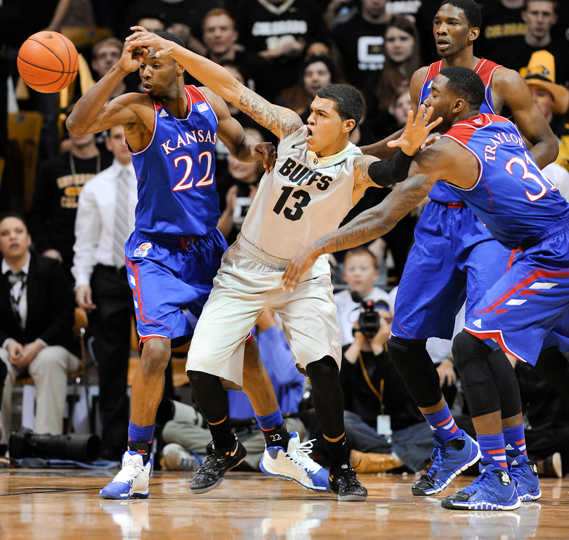 . Colorado University forward, Dustin Thomas, center, fights for control of the ball against Kansas defenders, Andrew Wiggins, left, and Jamari Traylor, right,  in the first half of play at the Coors Events Center in Boulder Colorado Saturday afternoon, December 07, 2013. (Photo By Andy Cross/The Denver Post)
