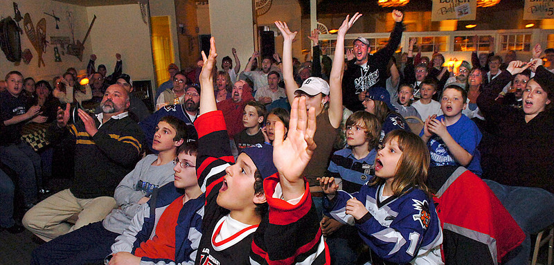 Fans celebrate one of three first period goals the Lewiston Maineiacs scored against the Halifax Mooseheads during game 5 of their playoff series.  Over 100 fans watched the game on closed several large screens set up at the Ramada Inn in Lewiston for fans to watch their home town heroes.