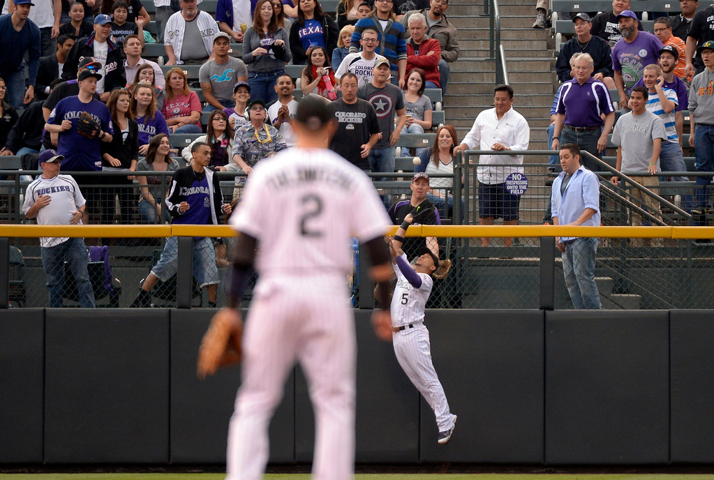 . DENVER, CO - MAY 06: Colorado Rockies left fielder Carlos Gonzalez (5) catches a fly ball at the fence on a hit by Texas Rangers catcher J.P. Arencibia (7) May 6, 2014 at Coors Field. Gonzalez made the catch for the third out. (Photo by John Leyba/The Denver Post)