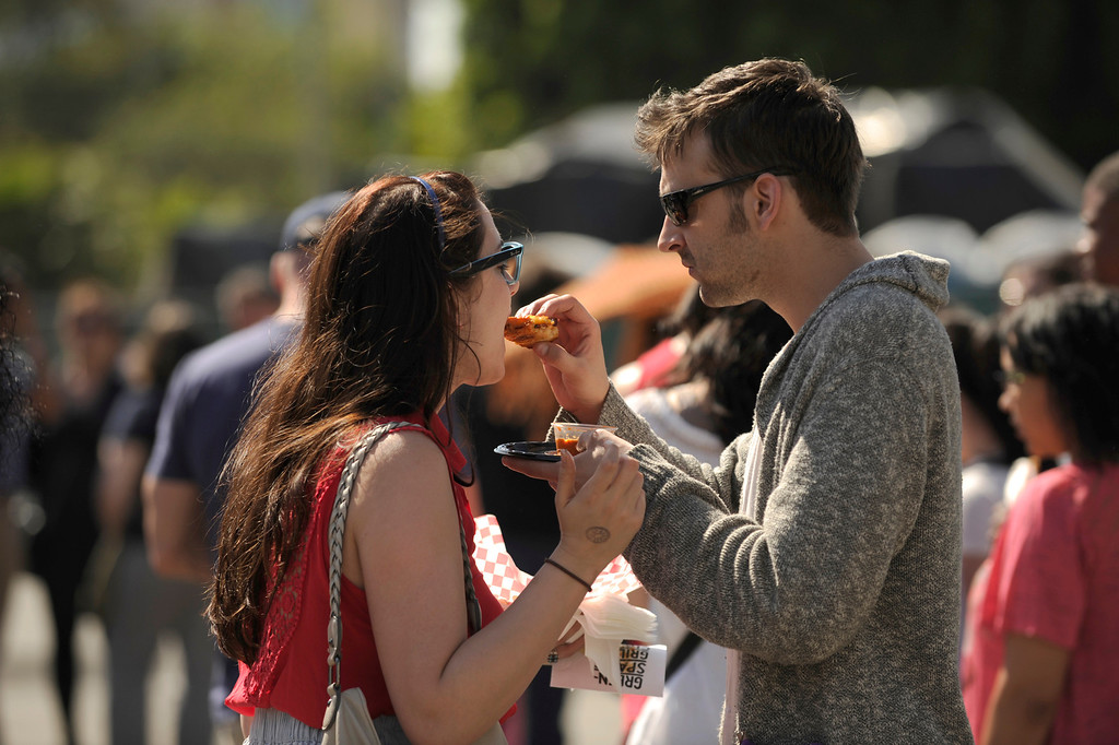 . Kris Karr and Logan Pietz share a sammy. The 11th Annual Grilled Cheese Invitational was held Saturday at the Los Angeles Center Studios, 1201 W. 5th Street, in downtown. Cheese lovers came together to sample grilled cheese sandwiches in a variety of incarnations. Los Angeles, CA 4/20/2013(John McCoy/Staff Photographer
