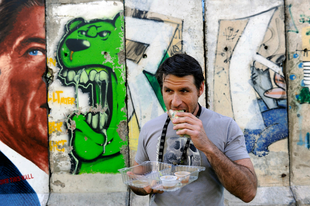 . Brian Meredith eats a chicken spring roll from the food trucks on Wilshire Boulevard across from the Los Angeles County Museum of Art, Wednesday, April 10, 2013. He is eating at sections of the Berlin Wall. (Michael Owen Baker/Staff Photographer)