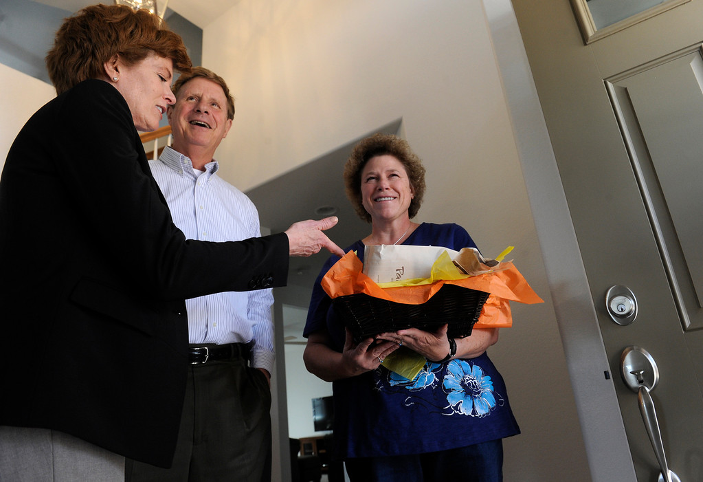 . Melissa Mizelle, right, is given a special gift basket from the mayor and his wife as they are invited in to Mizelle\'s newly built home. Mizelle had just move in to the house that week.  (Photo By Kathryn Scott Osler/The Denver Post)