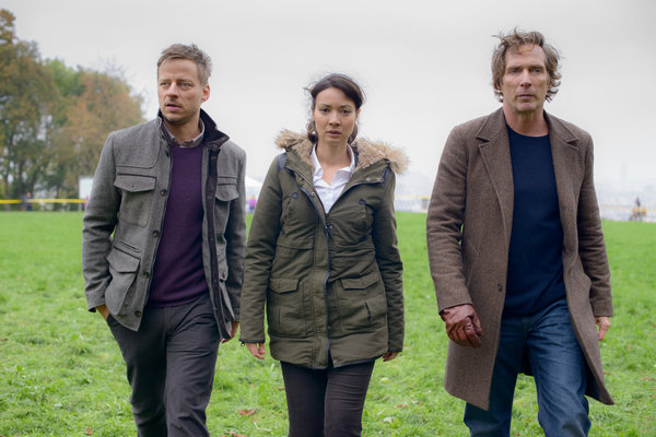 """. CROSSING LINES -- \""""Pilot - Part I\"""" Episode 101 -- Pictured: (l-r) Tom Wlaschiha as Sebastian Berger, Moon Dailly as Anne-Marie San, William Fichtner as Carl Hickman -- (Photo by: Etienne Chognard/Tandem)"""