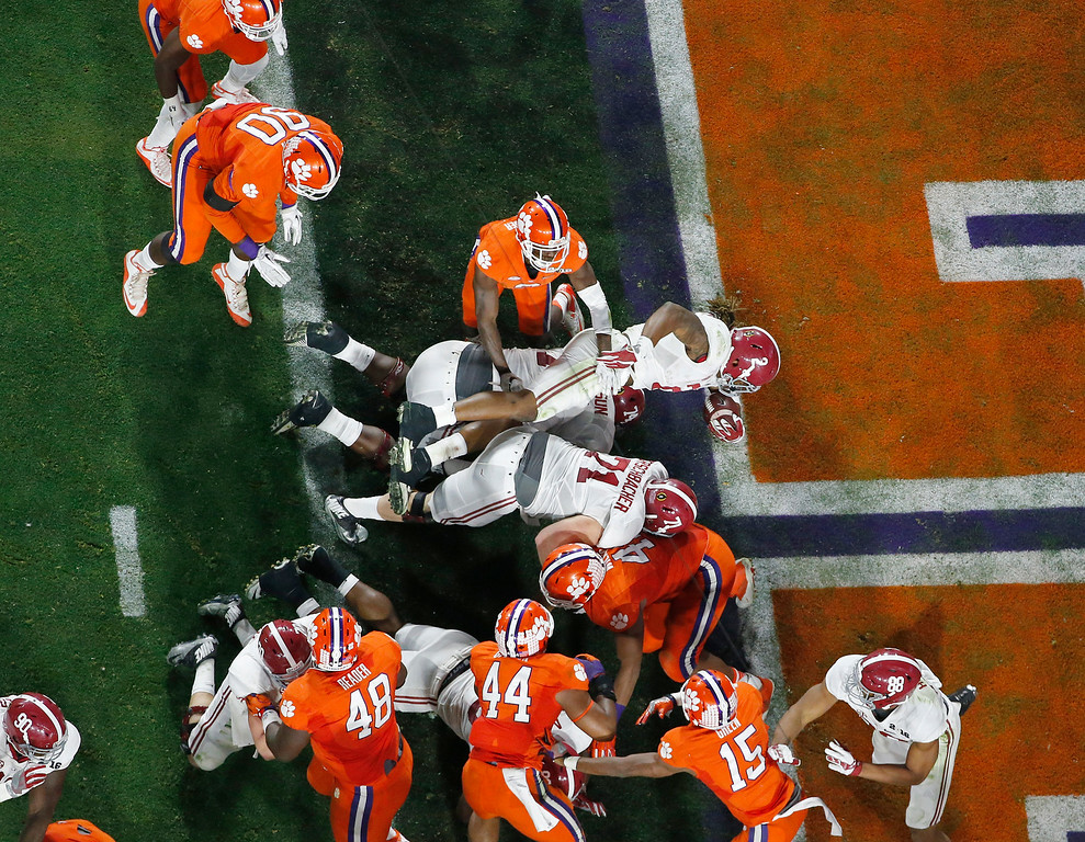 . Alabama\'s Derrick Henry, center, dives into the end zone for a touchdown run during the first half of the NCAA college football playoff championship game against Clemson Monday, Jan. 11, 2016, in Glendale, Ariz. (AP Photo/Ross D. Franklin)