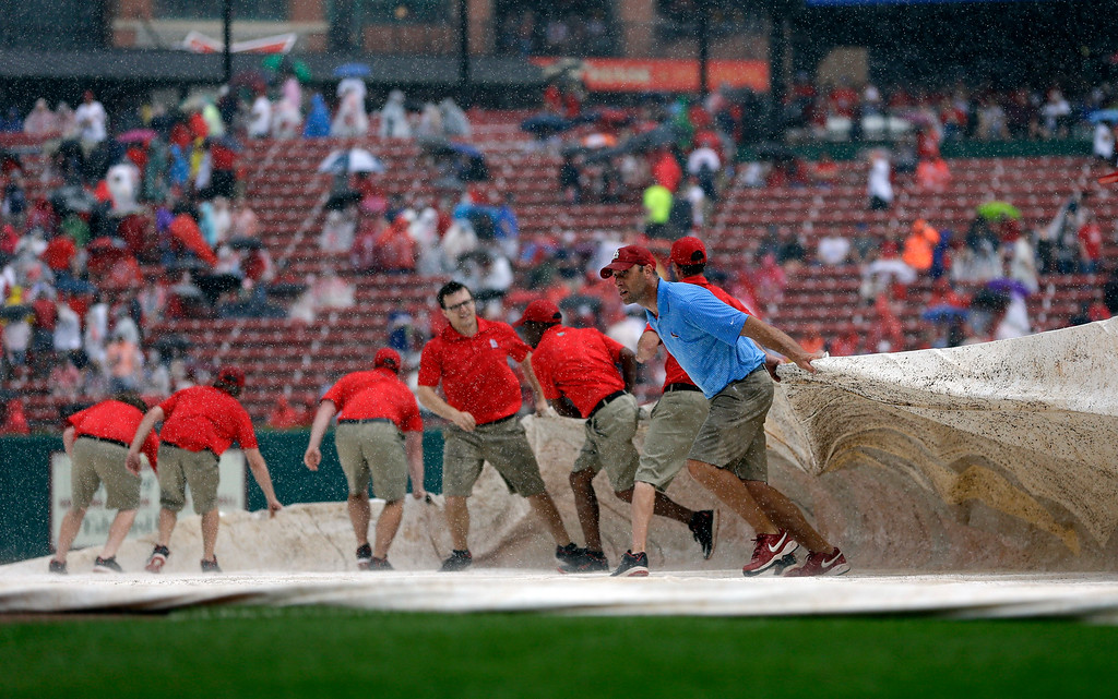 . Members of the Busch Stadium grounds crew pull a tarp over the field at the start of a rain delay during the first inning of a baseball game between the St. Louis Cardinals and the Detroit Tigers Saturday, May 16, 2015, in St. Louis. (AP Photo/Jeff Roberson)