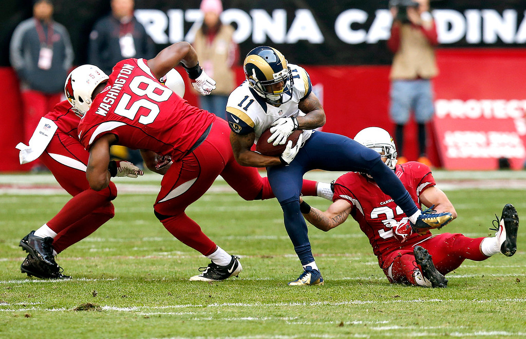 . St. Louis Rams wide receiver Tavon Austin (11) is tripped up by Arizona Cardinals inside linebacker Daryl Washington (58), Tyrann Mathieu (32) and Rashad Johnson, left, during the first half of an NFL football game, Sunday, Dec. 8, 2013, in Glendale, Ariz. (AP Photo/Ross D. Franklin)