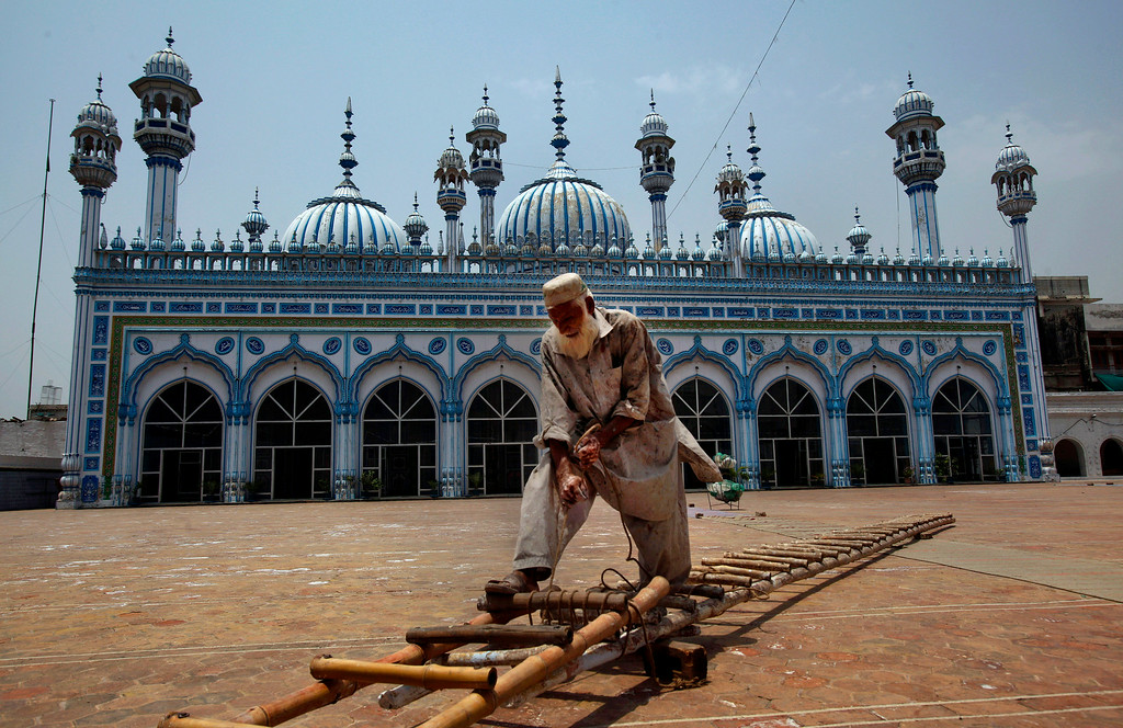 . A painter fixes a ladder to whitewash the outer wall of a mosque in preparation for upcoming Islamic holy month of Ramadan in Rawalpindi, Pakistan, Saturday, July 28, 2014. Muslims throughout the world are preparing to celebrate the holy fasting month of Ramadan, when they refrain from eating, drinking, and smoking from dawn to dusk. Muslims usually increase their religious activities during the Ramadan. (AP Photo/Anjum Naveed)