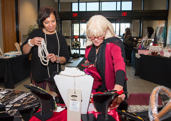 12/12/19 Wesley Bunnell | StaffrrOwner Pat Davis, L, of Sophisticaed Glamor, assists customer Patrice Adams during the Holiday Craft Fair at 1 Liberty Square on Thursday afternoon.