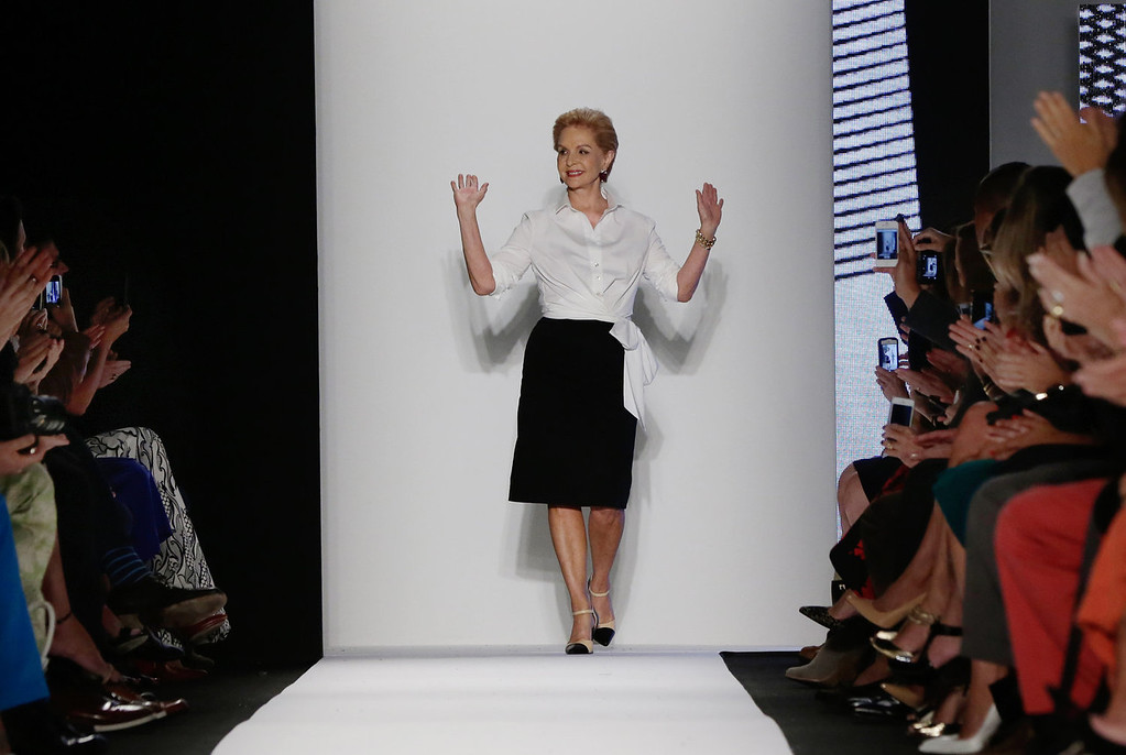 . Designer Carolina Herrera acknowledges audience applause after her Spring 2014 collection was modeled during Fashion Week in New York,  Monday, Sept. 9, 2013. (AP Photo/Richard Drew)