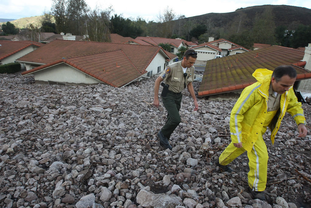 . Ventura County Sheriffs deputies walk on piles of rocks and mud after debris flows smashed into homes as a powerful storm that has been lashing northern California moves southward on December 12, 2014 in Camarillo Springs neighborhood of Camarilla, California. About two dozen homes were severely damage in a heavy pre-dawn downpour. Although water from the storm lowers the risk of wildfires and offers some short-term relief from the record drought conditions that are menacing the state, weather experts say it amounts to only a very small step toward ending the drought.   (Photo by David McNew/Getty Images)