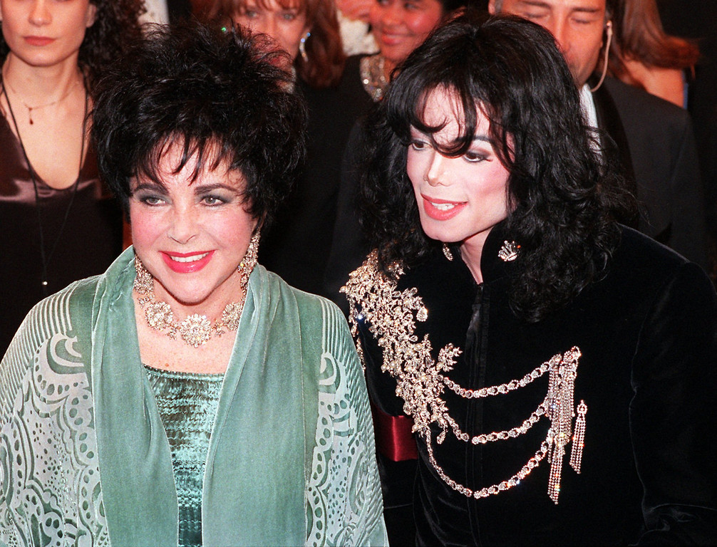 . Elizabeth Taylor arrives with her friend Michael Jackson at the Pantages Theater in the Hollywood area of Los Angeles Sunday, Feb. 16, 1997, prior to the start of a birthday celebration for Taylor. (AP Photo/Chris Pizzello)