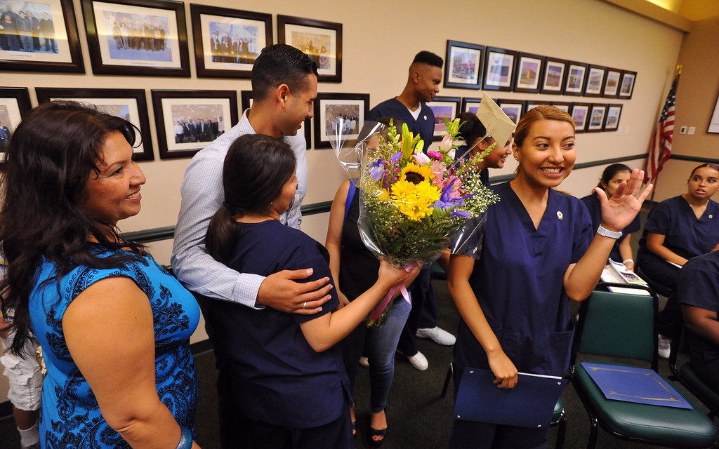 . 10 recent high school graduates are congratulated by family members after receiving their Certified Nursing Assistant certificates at the Goodwill in Long Beach, CA on Friday, August 22, 2014. The students; Gabriela Avila, Averianna Burnett, Alesia Clay, Ariana Mays, Kendra Montano, Silvia Monzon, Genesis Perez, Cindia Sanchez, Daniel Scott and Dahlia You completed the year-long course in a partnership between the LBUSD and Goodwill. This is the first year that the state Certified Nurse Assistant Training Academy program has been free for the students. It was announced to the families and friends gathered that all 10 of the graduates have health care job interviews next week. (Photo by Scott Varley, Daily Breeze)