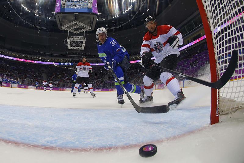 . Slovenia\'s Jan Mursak (C) scores against Austria\'s Gerhard Unterluggauer during the Men\'s Ice Hockey Play-offs Solovenia vs Austria at the Bolshoy Ice Dome during the Sochi Winter Olympics on February 18, 2014. Slovenia won 4-0.  (MARK BLINCH/AFP/Getty Images)