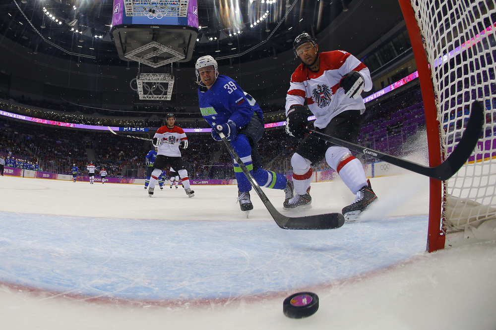 . Slovenia\'s Jan Mursak (C) scores against Austria\'s Gerhard Unterluggauer during the Men\'s Ice Hockey Play-offs Solovenia vs Austria at the Bolshoy Ice Dome during the Sochi Winter Olympics on February 18, 2014. Slovenia won 4-0.  (MARK BLINCH/AFP/Getty Images)