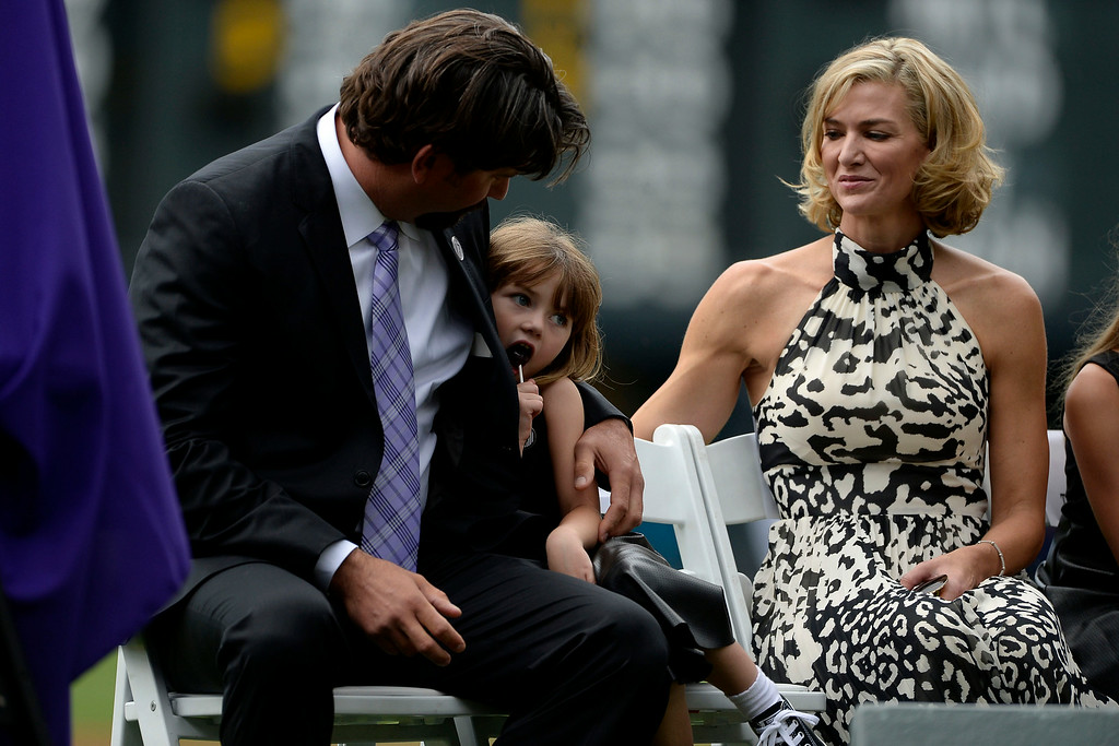 . Colorado Rockies great Todd Helton holds his daughter, Gentry Grace, as they sit by his wife, Christy, during a retirement ceremony for his number 17. Helton, who played 17 season with the Rockies and holds records for many of the organizations career statistics, was honored on Sunday, August 17, 2014. (Photo by AAron Ontiveroz/The Denver Post)