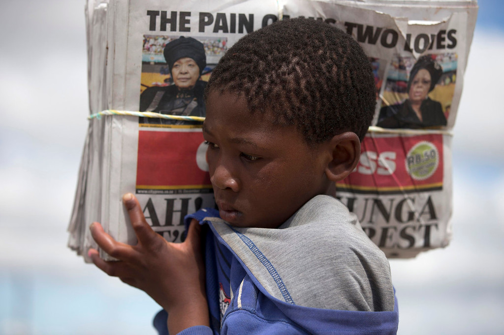""". A young boy carries a stack of newspapers with a picture of Winnie Madikizela-Mandela, left, Nelson Mandela\'s former wife, and Nelson Mandelaís widow Graca Machel, right,  with a headline reading \""""The Pain Of His Two Loves\"""" during the burial of the former South African President and iconic leader in his hometown Qunu, South Africa, Sunday Dec. 15, 2013. (AP Photo/Peter Dejong)"""