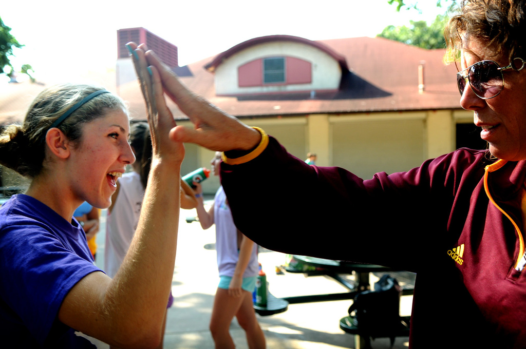 . Freshman Maria Valenti, left, gets a high five from assistant coach Tracy Angelo before she takes off on a run during a team practice at Minnehaha Falls Park. (Pioneer Press: Jean Pieri)