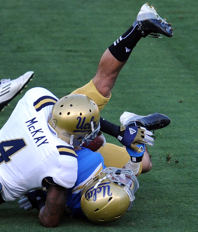. UCLA tight end Grayson Mazzone (83) is tackled by UCLA safety Stan McKay (4) during the football spring showcase college football game in the Rose Bowl on Saturday, April 27, 2013 in Pasadena, Calif.    (Keith Birmingham Pasadena Star-News)