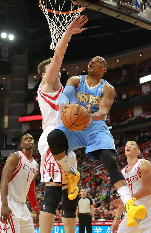 . Denver Nuggets guard Randy Foye goes up for a shot against Houston Rockets center Omer Asik as Rockets\' Terrence Jones and Jeremy Lin, right, watch during the first half of an NBA basketball game in Houston on Sunday, April 6, 2014. (AP Photo/Richard Carson)