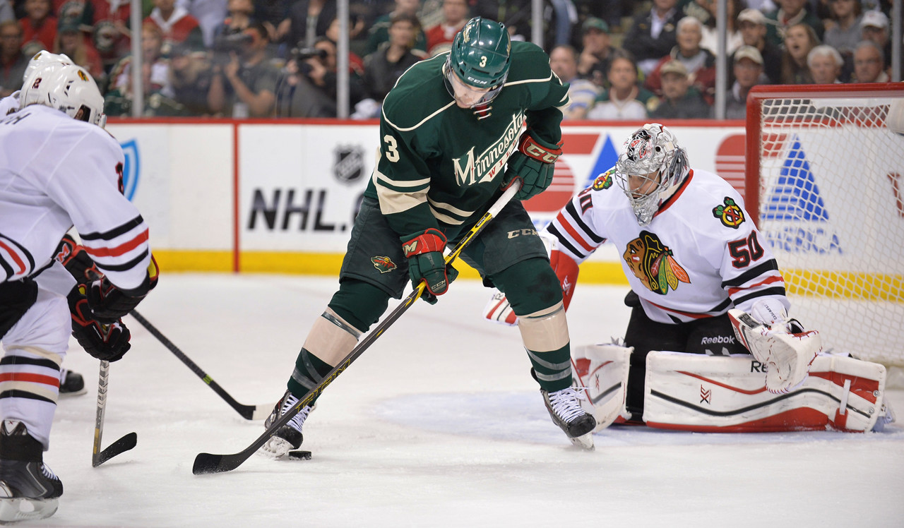 . Minnesota\'s Charlie Coyle, left, tries to get his stick on the puck as Blackhawks goalie Corey Crawford spreads his blockers during the first period. (Pioneer Press: Ben Garvin)