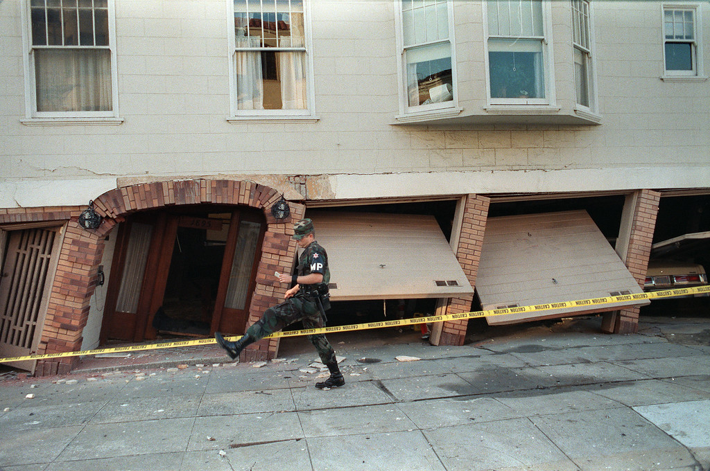 . A military policeman steps over a police line on October 18, 1989, in front of a heavily-damaged building in the Marina District of San Francisco, one of the areas hardest hit in the city by a 6.9 earthquake on October 17, 1989. (ADAM TEITELBAUM/AFP/Getty Images)