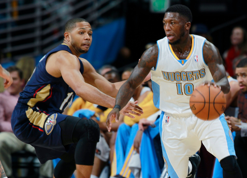 . Denver Nuggets guard Nate Robinson, right, slips past New Orleans Pelicans guard Eric Gordon late in the fourth quarter of the Nuggets\' 102-93 victory in an NBA basketball game in Denver on Sunday, Dec. 15, 2013. (AP Photo/David Zalubowski)