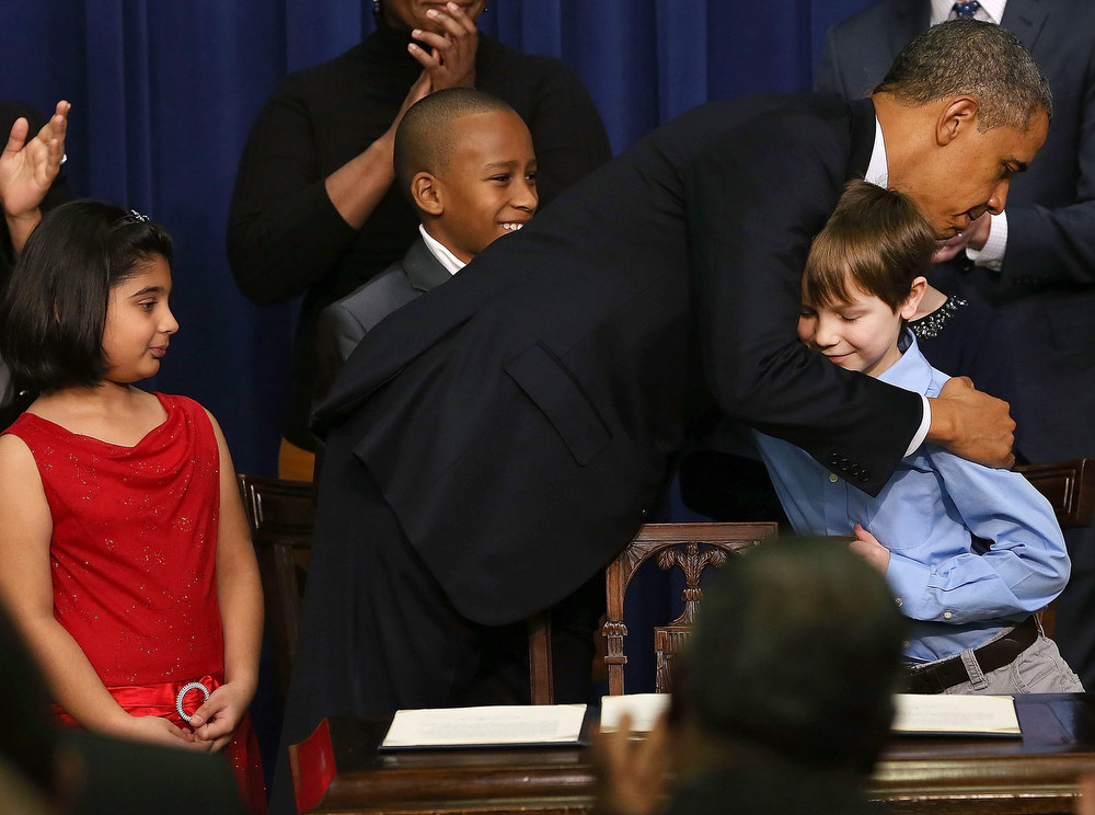 Description of . U.S. President Barack Obama hugs children who wrote letters to the White House about gun violence, (L-R) Hinna Zeejah, Taejah Goode, and Grant Fritz, after announcing the administration's new gun law proposals in the Eisenhower Executive Office building, on January 16, 2012 in Washington, DC. One month after a massacre that left 20 school children and 6 adults dead in Newtown, Connecticut, the president unveiled a package of gun control proposals that include universal background checks and bans on assault weapons and high-capacity magazines.  (Photo by Mark Wilson/Getty Images)