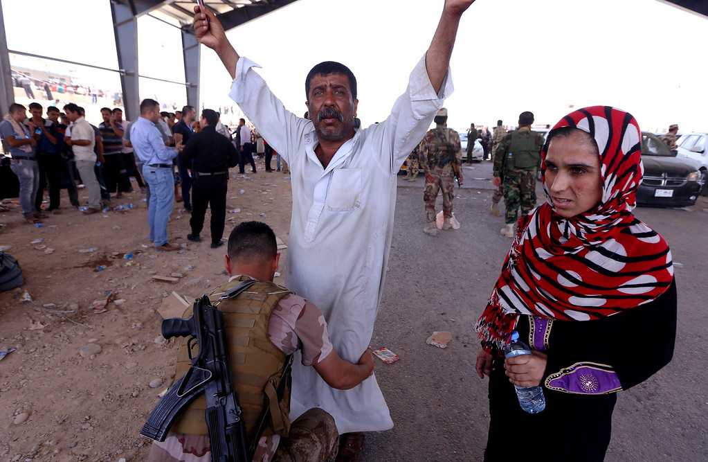 . An Iraqi Kurdish security guard frisks a man as families fleeing violence in Iraq\'s northern Nineveh province wait in their vehicles at a Kurdish checkpoint in Aski kalak, 40 kms West of Arbil, in the autonomous Kurdistan region, on June 10, 2014. Suspected jihadists seized Iraq\'s entire northern province of Nineveh and its capital Mosul, the country\'s second-largest city, in a major blow to authorities, who appear incapable of stopping militant advances. SAFIN HAMED/AFP/Getty Images