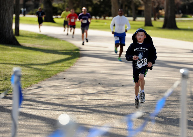 . Travis Guzman, 10, makes his way to the finish of the race.  His father Anthony Guzman is a detective with the Denver Police Department.  Family, colleagues, and friends of slain Denver Police Officer Celena Hollis turned out April 7, 2013 for a 5k run and walk to raise money for a scholarship fun and a memorial bench in City Park in Denver, CO.  Over 300 runners and walkers participated in the race that started at 9:00 am.  The race looped around City Park.  After the race, a gathering was held to remember Hollis and 22 white doves were released in her memory.  (Photo By Helen H. Richardson/ The Denver Post)