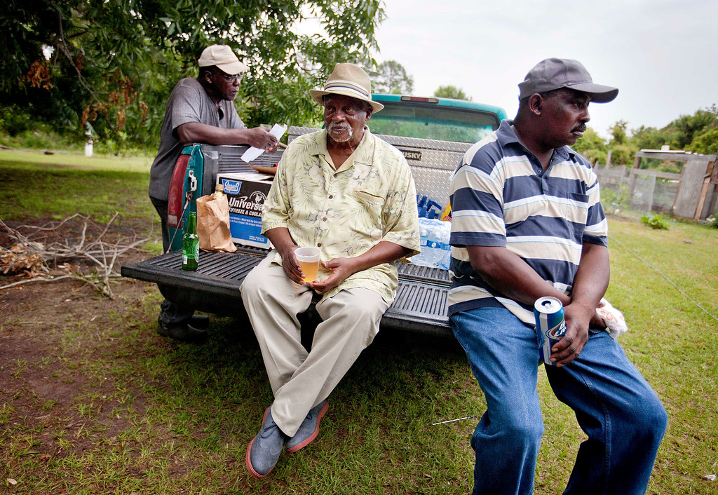""". Richard Dixon, 70, center, on a visit to his native Sapelo Island from Los Angeles, sits with Sapelo residents Julius Bailey, left, and Herman Dixon, right, after a church service on Sapelo Island, Ga. on Sunday, June 9, 2013. \""""Everyone feels like family here,\"""" says Richard Dixon, \""""I\'ll fight along with everyone else because this will always be my home.\"""" (AP Photo/David Goldman)"""
