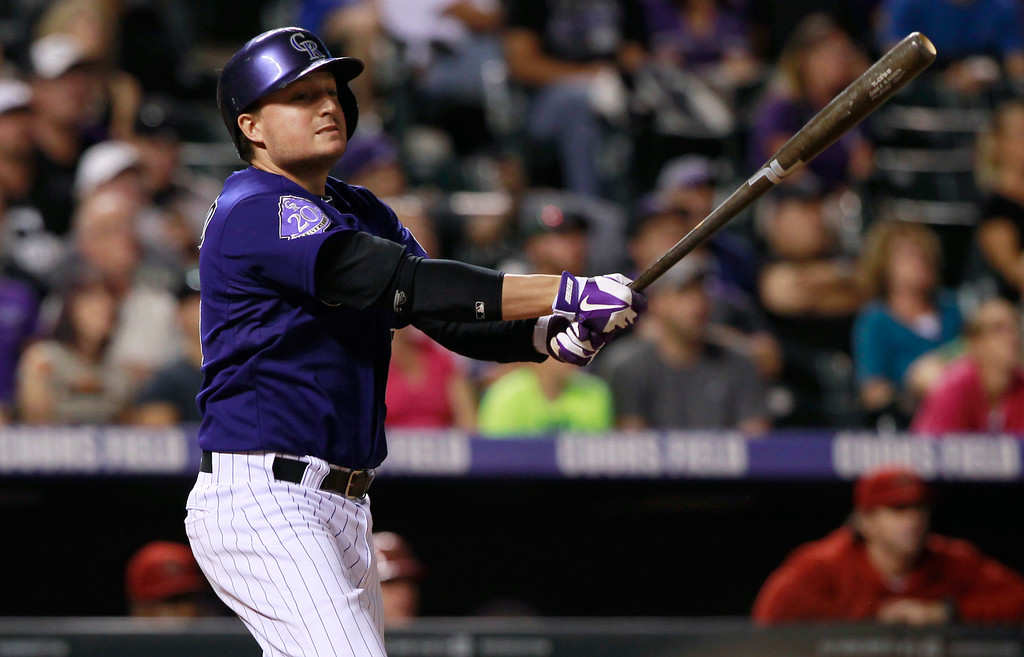 . Colorado Rockies\' Jordan Pacheco follows the flight of his sacrifice fly to drive in a run against the Arizona Diamondbacks in the fourth inning of a baseball game in Denver on Saturday, Sept. 21, 2013. (AP Photo/David Zalubowski)