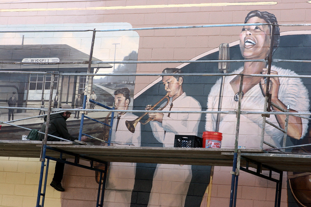 . Artist Josh Powell paints a section of his new mural along A Street at Maple Court in Hayward, Calif. Friday Jan. 13, 2012. The mural with a Russel City theme joins other murals painted by Powell and many other local artists through out the City of Hayward. (Anda Chu/Staff Archives)