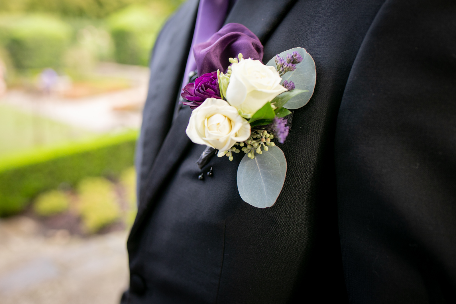 A close up of a grooms purple and white real flower boutonniere