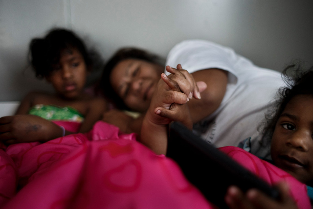 . Clarissa Taitano, center, comforts her 3-year-old daughter I\'Yannah Jackson as her older daughter, A\'Riyah Jackson, 5, left, stays by her mother, in their mobile home on May 24, 2013, in San Jose. The family recently moved to their mobile home after living in a Santa Clara motel for 64 days. (Dai Sugano/Bay Area News Group)