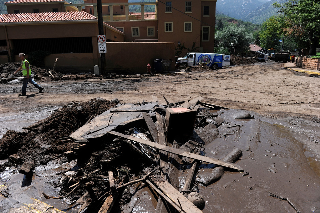 . MANITOU SPRINGS, CO - Aug.10: Residents and crews clean up the damage and debris along Canon Avenue after a flash flood roared through the streets and hillsides on Friday evening. (Photo By Kathryn Scott Osler/The Denver Post)