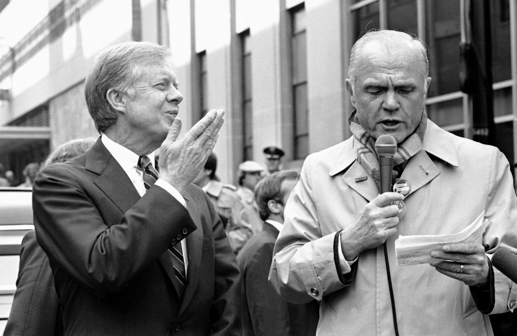 . U.S. President Jimmy Carter blows a kiss to a spectator as Senator John Glenn (D-Ohio) speaks about Carter at rally in Youngstown, Ohio on Monday, Oct. 20, 1980. It was a significant meeting for Carter, who has enlisted only lukewarm support from Glenn in the past. After this rally, Carter appeared for an hour on live television, answering questions from a small audience. (AP Photo/Wilson)