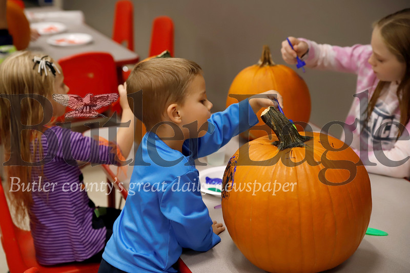 Grady,4 (Front), Ella, 4(left), and Ema Demitras, 10  paint pumpkins at the Butler YMCA's Floating Pumpkin Patch event Saturday. Seb Foltz/Butler Eagle