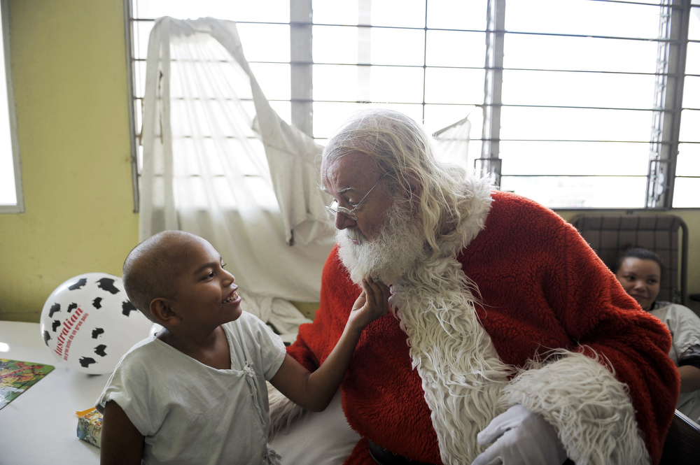 Description of . Icelandic philantropist Einar Sveinsson, dressed as Santa Claus, speaks with a patient at the oncology ward during a visit to the Benjamin Bloom National Children Hospital, in San Salvador, on December 11, 2012. Sveinsson visits the hospital prior to Christmas every year since 2001 to give gifts to the patients.  Jose CABEZAS/AFP/Getty Images
